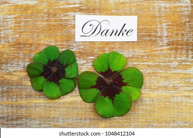 Danke (thank you in German) card with two shamrocks on wooden surface