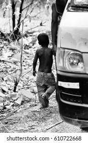 DANKOLI, BENIN - JAN 12, 2017: Unidentified Beninese little booy walks near a car in the village. People of Benin suffer of poverty due to the bad economy
