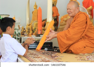 Dansai, Loei / Thailand - July 10, 2019 : A representative of school students offers a Buddhist monk a giant candle on the important Buddhist holy occasion call the Buddhist Lent Period