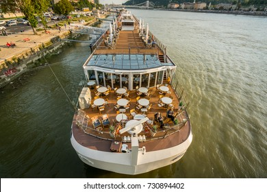 Danube cruise ship. Budapest, Hungary - September 26, 2017: Wide view of Viking Cruises canal boat cruise ship at the Danube river in Budapest. Passengers on deck outdoors to relax and people ashore.