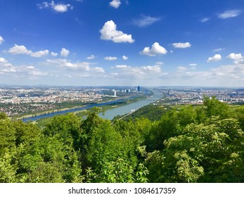 Danube river Donau Canal viewed from Vienna Woods on Clear summer day with blue sky and cotton clouds, City of Vienna in Background