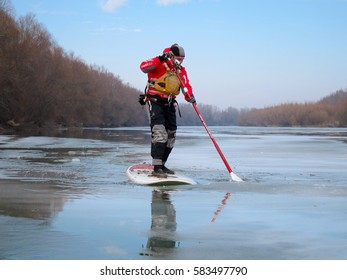 DANUBE RIVER, UKRAINE - FEBRUARY 04, 2017: Man standing on kayak SUP. Winter kayaking on icy frozen Danube river.