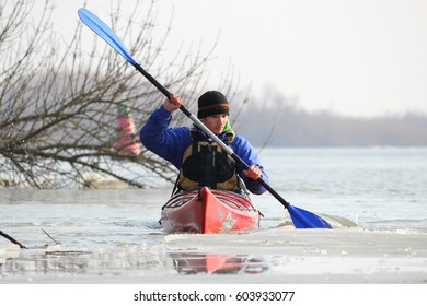 DANUBE RIVER, UKRAINE - FEBRUARY 18, 2017: Guy in red kayak in winter Danube river. Winter kayaking