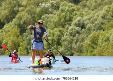 DANUBE RIVER, UKRAINE - JULY 14, 2017: Water tourists is paddling on SUP ( Stand up paddle board) and kayaks at Danube river on biosphere reserve in spring. Concept of water tourism