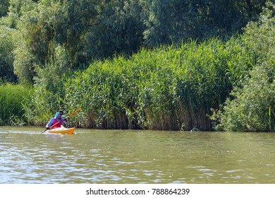 DANUBE RIVER, UKRAINE - JULY 14, 2017: Man in yellow kayak paddling at river on biosphere reserve in spring. Kayaking in Danube river. Concept for adventure, travel, action, lifestyle