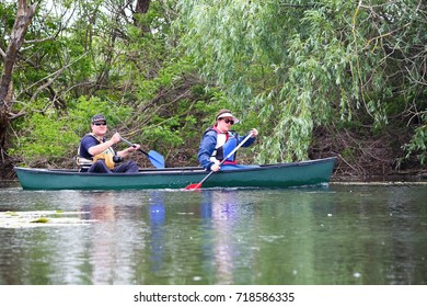DANUBE RIVER, UKRAINE - MAY 20, 2017: Couple man and a woman paddle in canoe among green wild thickets of plants in Danube river biosphere reserve