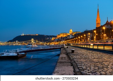 Danube waterfront in Pest with a view over Chain Bridge and Buda Castle at night, Budapest, Hungary. Caption on the walkaway has pattern with Chain Bridge, which was taken from the image itself.
