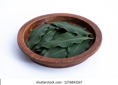 Daphne leaves. Group of daphne leaves isolated on white surface. Daphne leaves in the wooden plate.