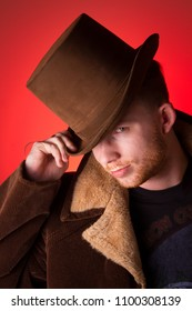 Dapper man in a top hat staring into the camera, tipping his hat. Red background.