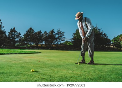 A dapper mature bearded black guy in an elegant outfit and a hat, with a cigar in his mouth, is standing on a green lawn of a golf field is ready to hit a ball using a club on a warm sunny evening