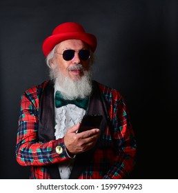 A dapper old gentleman with a red bowler hat, fake tuxedo and aviator sunglasses working his smartphone and reacting with facial expressions. Old Caucasian with a red bowler hat using his cellphone.