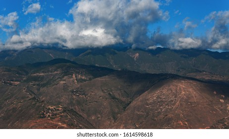 A dappled hillside is covered with blue sky and clouds in a mountainous area in southwest China
