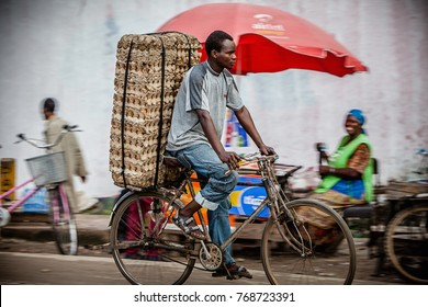 Dar es Salaam, Tanzania, Africa, circa May 2013. An unidentified man rides a bicycle on a market road in Dar es Salaam, transporting a large stack of egg cartons. Protein deficiency is an issue here.