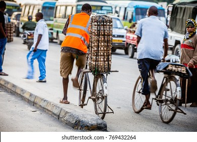 Dar es Salaam, Tanzania, Africa, circa May 2013:  An unidentified man pushes a bicycle in Dar es Salaam.  The city has major infrastructural problems, including an outdated transportation system.