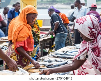 DAR ES SALAAM, TANZANIA - JANUARY 15, 2015: Local women buying seafood in the Mzizima fish market in Dar es Salaam, Tanzania in East Africa on Sunday. Landscape orientation.