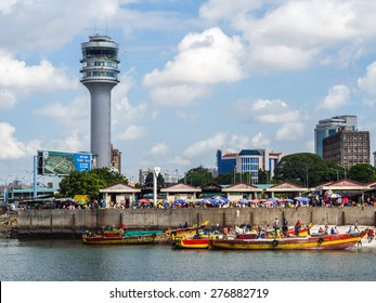 DAR ES SALAAM, TANZANIA - MAY 01, 2015: Horizontal photo of the waterfront of Dar es Salaam, Tanzania in East Africa, with maritime control tower and the fish market. Local people on boats in front.