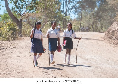 DARE, EAST TIMOR - JUNE 24, 2015: A group of young students are walking to school at noon on the dusty street. Walking a long distance is the most common way to go to school in the country.