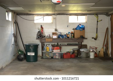Darien, Illinois, USA, August 14, 2017. The interior of an attached car garage on a house containing yard keeping tools, cleaning products, a trash can and miscellaneous other items.