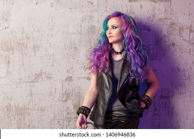 Daring rebel rocker, a portrait on a background of gray grunge wall. Young stylish woman in black leather clothes with colored hair. Bright hair coloring