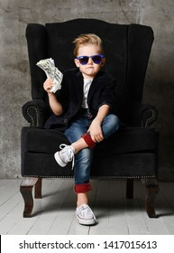 Daring and sassy young rich boy kid millionaire sits in big luxury armchair and demonstrates bundle of money dollar bills