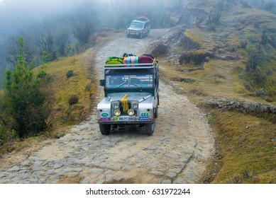 DARJEELING, INDIA - NOVEMBER 28, 2016: two jeeps climb a gravel road through Singalila National Park.  It is the route to Sankakphu and Phalut, the two highest peaks of Singalila range.
