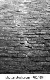 dark alley with cobblestones and water running down the middle in black and white