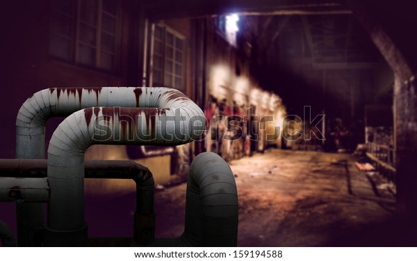 Dark alley with rusty pipes in foreground