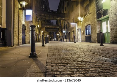 dark alley wide angle - Stock Image. London traditional old stone paved road at night VINTAGE
