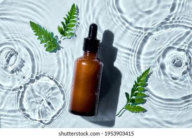 Bouteille de verre brun foncé flacon cosmétique de flacon pour soins de la peau crème de visage et gel douche de lotion du corps cosmétique naturel organique dans l'eau goutte pure belle.