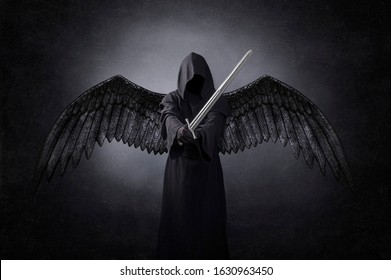 Dark angel with medieval sword in the dark