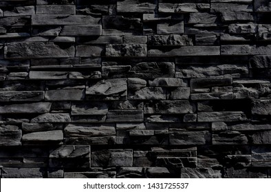 Dark anthracite gray, almost black texture of a wall made of horizontal slim cut stone blocks.