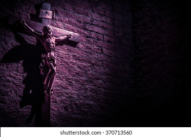 Dark artistic purple shade  monotone cross on a rough textured brick wall, lit by a sun ray with copy space for text.