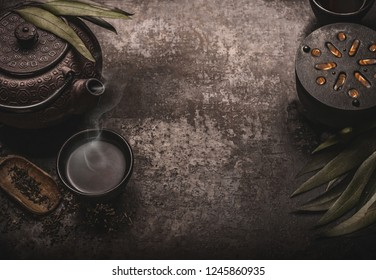 Dark asian tea background with black iron teapot and mug of green tea. Copy space for your design. Authentic vintage style. Traditional tea ceremony arrangement