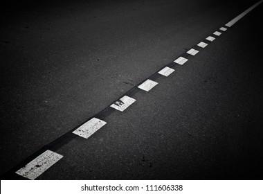 Dark asphalt road background with marking lines. Close up photo