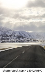 Dark asphalt road on the background of mountains and ocean. The tour around Iceland. Geothermal heat this way.