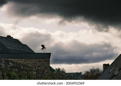 Dark atmosphere. Weathervane in the form of cupid turn to black cloud and old stone