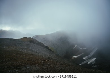 Dark atmospheric landscape on edge of abyss in highlands. Dangerous mountains and abyss among low clouds. Danger mountain pass and sharp rocks in clouds. Dangerous cloudy rainy weather in mountains.