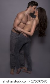 Dark atmospheric studio portrait of a sexy topless couple enjoying a passionate kiss in a romantic embrace