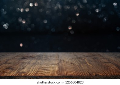 Dark background with bright bokeh in front of a empty wooden table for festive decorations