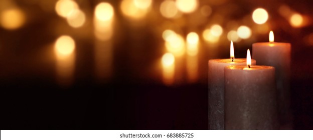 Dark background with burning candles and golden bokeh for christmas time