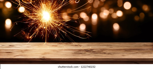 Dark background with festive bright bokeh and a sparkler in front of empty old wooden table for a christmas decoration