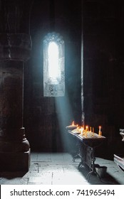 A dark background of old Armenian christian church monastery interior with a sun ray falling to the candles from a window. Abstract christian religion belief and travel concept.