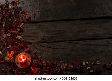 Dark background with red candle on vintage boards. Space for text.