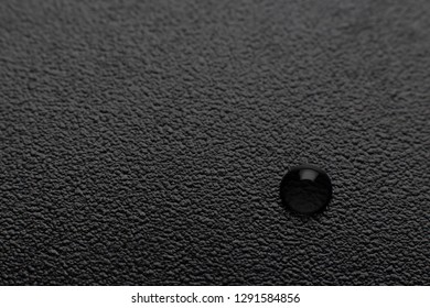 Dark background with a textured leather and a drop in the lower right corner. Blurry background.
