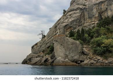Dark bare Rocks under the cloudy sunset. View from the Black sea, Novyi Svit, Crimea