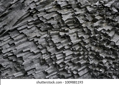 Dark basalt column formation in Iceland. Closeup. Horizontal.