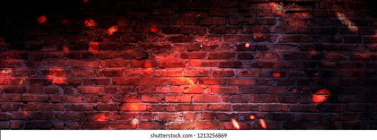 Dark basement room, sparks of fire and light on the walls. Neon lamps on the wall, night view. Empty brick wall.