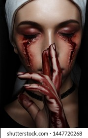 Dark beauty nun in burqa with black eyes with bloody stains and scars. Horror halloween concept of witch obsessed by the devil