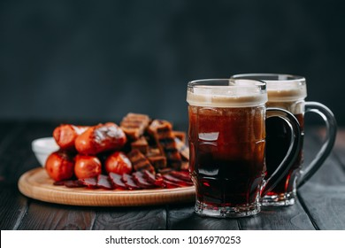 Dark beer and appetizing beer snacks set. Table with two mugs of stout, wooden board with grilled sausages, dried meat basturma and crunchy toasts, served with sauces. Oktoberfest food, pub concept