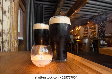 Dark beer and candle in pub setting